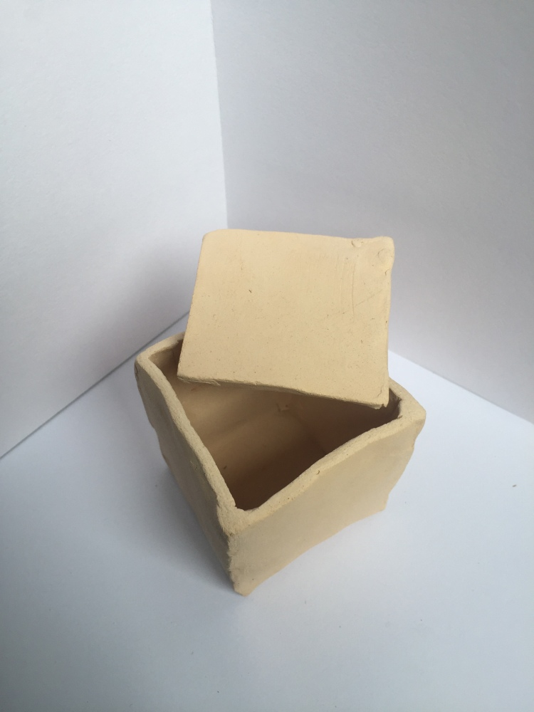 An open clay box with its lid resting on one edge of the top
